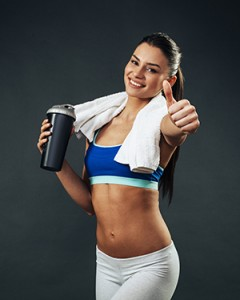 Attractive young woman with a protein shake holding thumbs up