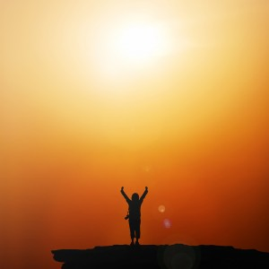 Silhouette of traveller with hands raised to the sun at  sunrise