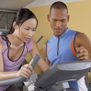 Trainer helping a woman with the cycle in a gym.