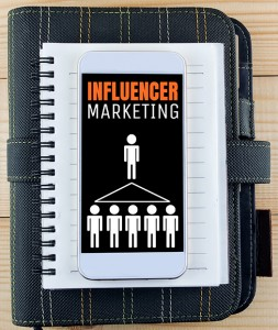notebook smart phone on wood background word influencer marketing