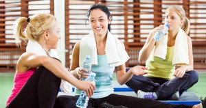 Happy women relaxing and talking after fitness training