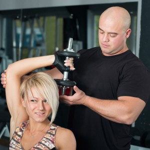 Woman lifting dumbbells with her personal trainer in the gym