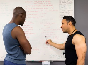 personal trainer teaching man in fitness classroom